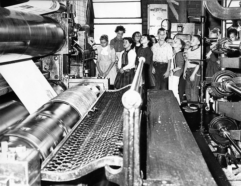 Students from Winnetka Avenue Elementary School in Canoga Park gaze in awe at huge cylindrical press and watch as white paper roll races between plates and is changed into Valley Times Today. Pressmen later gave paper hats to 37 members of school's B-3 class who toured newspaper.