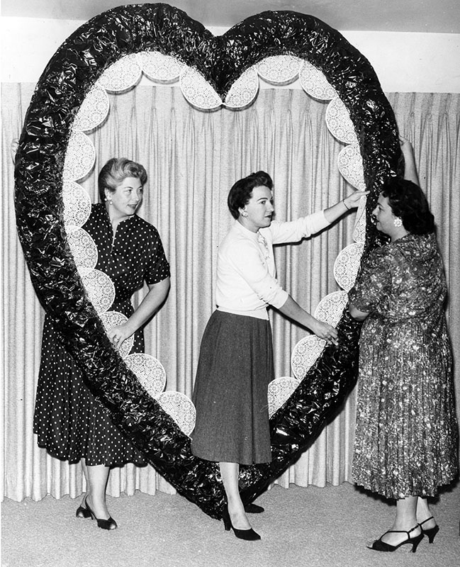 "Photograph caption dated February 6, 1958 reads, ""Personalities from the entertainment field will select the queen of 'Sweetheart Swing' at the Valentine ball of San Fernando Valley Council of Beta Sigma Phi. Finishing regal frame for Feb. 14 event in Satellite Room of Santa Monica's Miramar Hotel are Mmes. Rodney Scholtes; Fred E. Davidson and Fred Kimble."" Order #00109232"