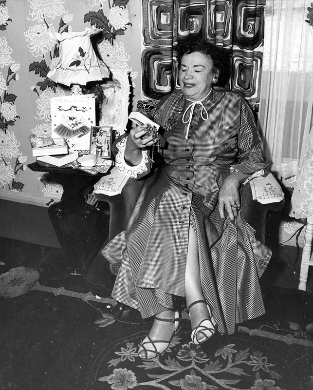 "Photograph caption dated March 17, 1956 reads, ""Mrs. Manley McCallum, of Tujunga, opens box of 'Luck o' the Irish' shamrocks sent to her direct from auld sod of Dublin, Ireland, in time for St. Patrick's Day. And they looked right in style. Mrs. McCallum came to United States from Ireland when she was 11."" Order #00109566"
