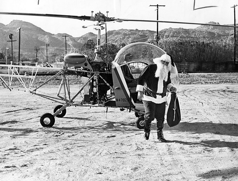 """Photograph caption dated December 15, 1964 reads """"The jolly old gentleman made a brief appearance at the Child Welfare Program in the Hughes Market parking lot, 21431 Devonshire St. The project was held to collect funds and toys for children and the needy. American Legion Post and its auxiliary, Chatsworth, sponsored annual project."""" Photo by Steve Young."""