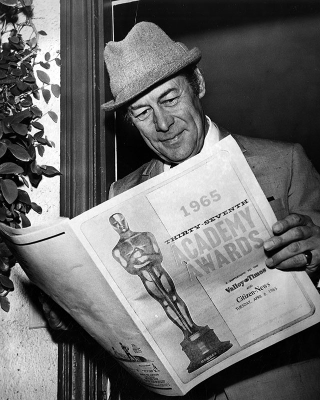 "Photograph caption dated April 8, 1965 reads, ""Academy award winner Rex Harrison reads the Valley Times' special Academy Awards section which reported all the colorful details of the 37th annual Oscar race. Rex is wearing his 'Mr. 'iggins' hat, one of the trademarks of his role in 'My Fair Lady' which won him the highly prized Oscar."" Photo by Peter Banks"