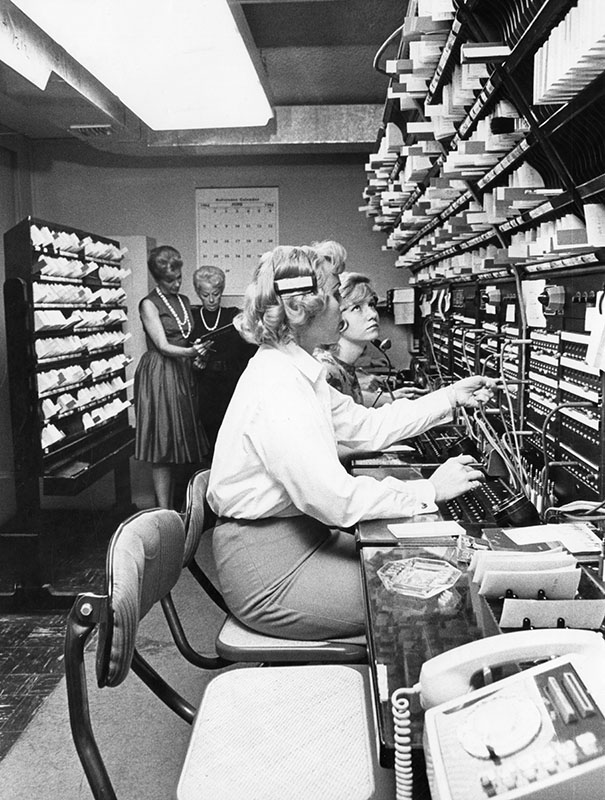 "Photograph caption dated June 29, 1964 reads, ""Twenty-five operators working three eight-hour shifts a day control the switchboard at Dial Faye. Services include everything from early morning wake-up calls to finding a trombone player for a studio musical. Second from left is proprietress Faye Pederson examining the day's schedule."" Photo by Steven Young"