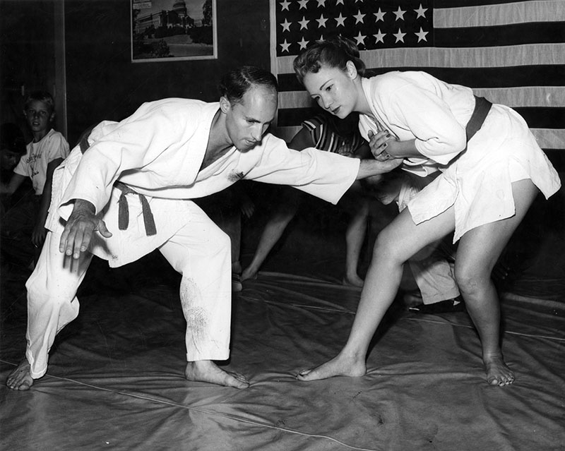 "Photograph caption dated July 17, 1956 reads, ""Carol Tegner, 19 and 5 foot 4, demonstrates elementary judo defense hold with James Widenot, another judo instructor. Carol has been teaching since she was 9. She's also expert skater, swimmer, tennis player and dancer."""