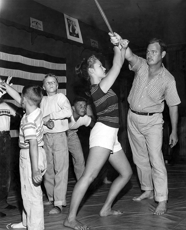 "Photograph caption dated July 17, 1956 reads, ""Size doesn't matter - 'Bigger they are, the harder they fall,' says Carol Tegner as she blocks club swung by George Cruse, of Northridge during Valley judo class."""