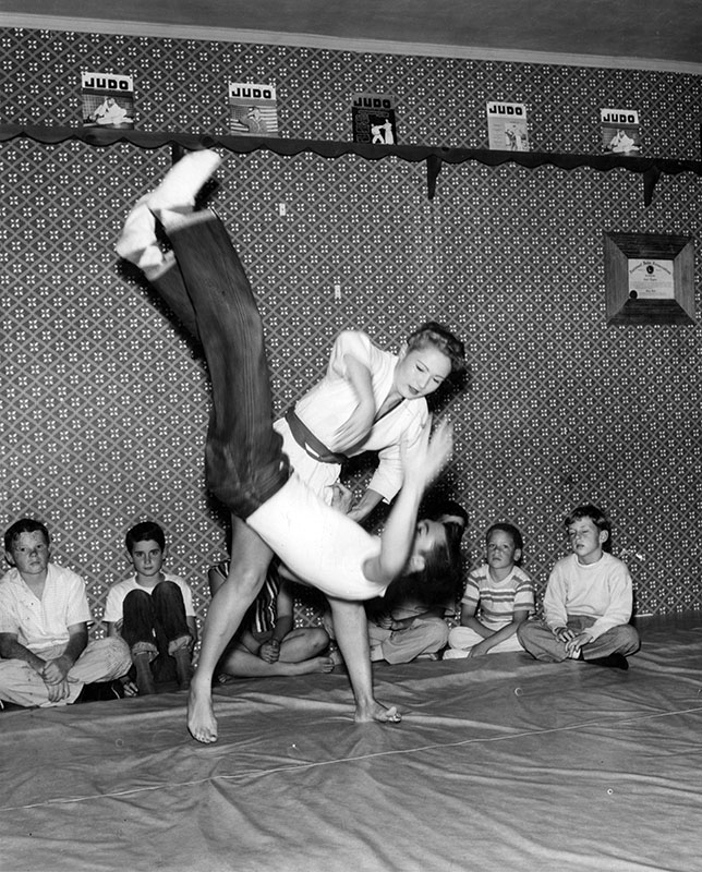 "Photograph caption dated July 17, 1956 reads, ""Up and over-Carol Tegner flips student Allen Smith, 18, of Pacoima, in spectacular over-the-shoulder throw in demonstration for students at school she operates with her brother Bruce. Their parents, too, are judo teachers."""